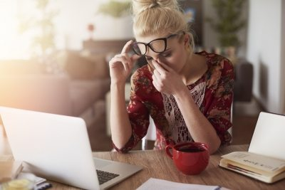 Woman working at home with a headache