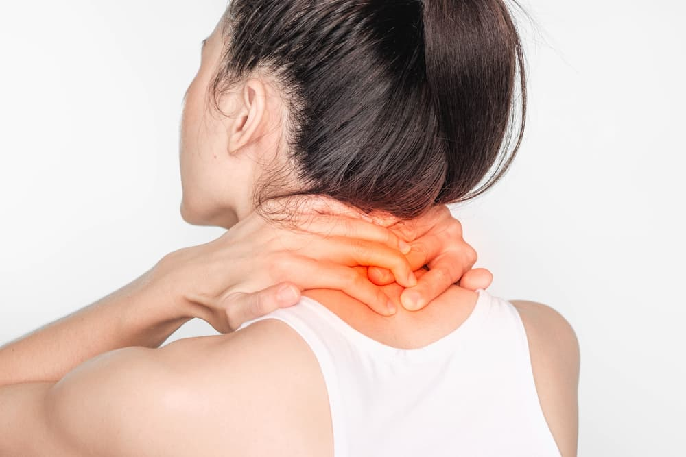 woman with neck pain. Female holding hand to spot of neck. Concept photo with read spot indicating location of the pain. Health-care concept