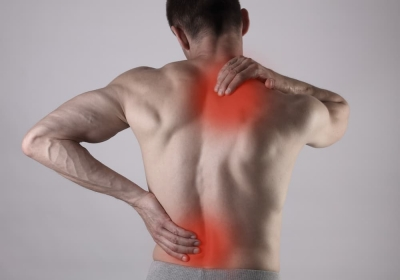 Muscular Man suffering from back and neck pain. Incorrect sitting posture problems Muscle spasm, rheumatism. Pain relief, chiropractic concept. Sport exercising injury